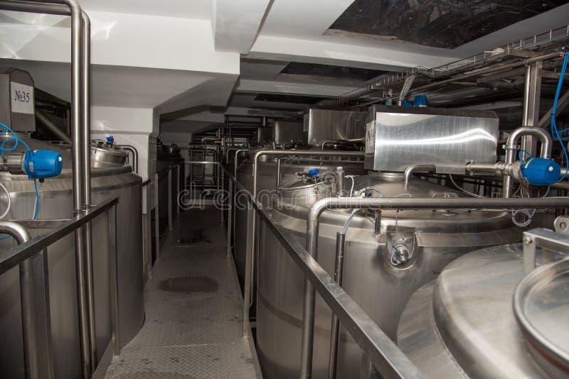 Grote blikken op moderne installatie voor productie van melk stock foto's