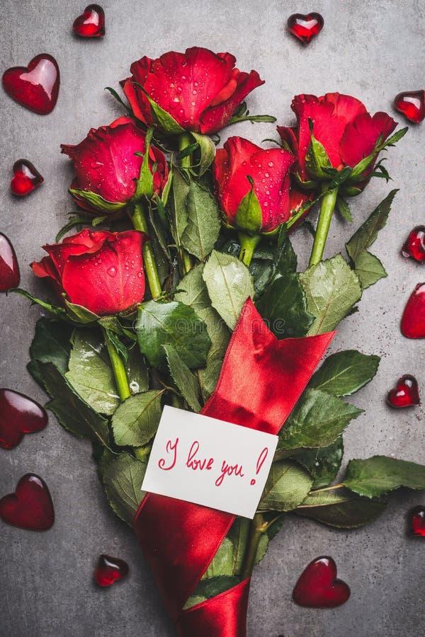 Grote bloemenbos met rode rozen, lint, houd ik van u van letters voorziende kaart en harten op grijze achtergrond stock fotografie