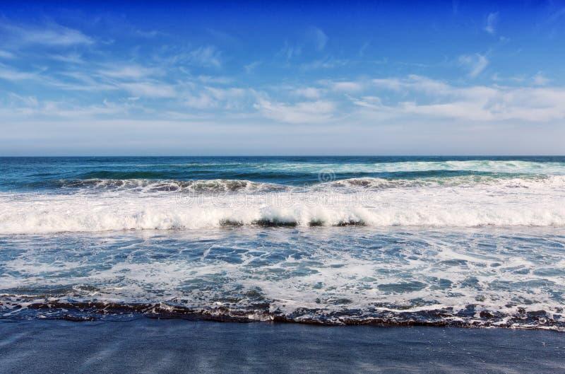 Grote brekende Oceaangolf op een zwart zandig strand op Vreedzame oceaan stock fotografie
