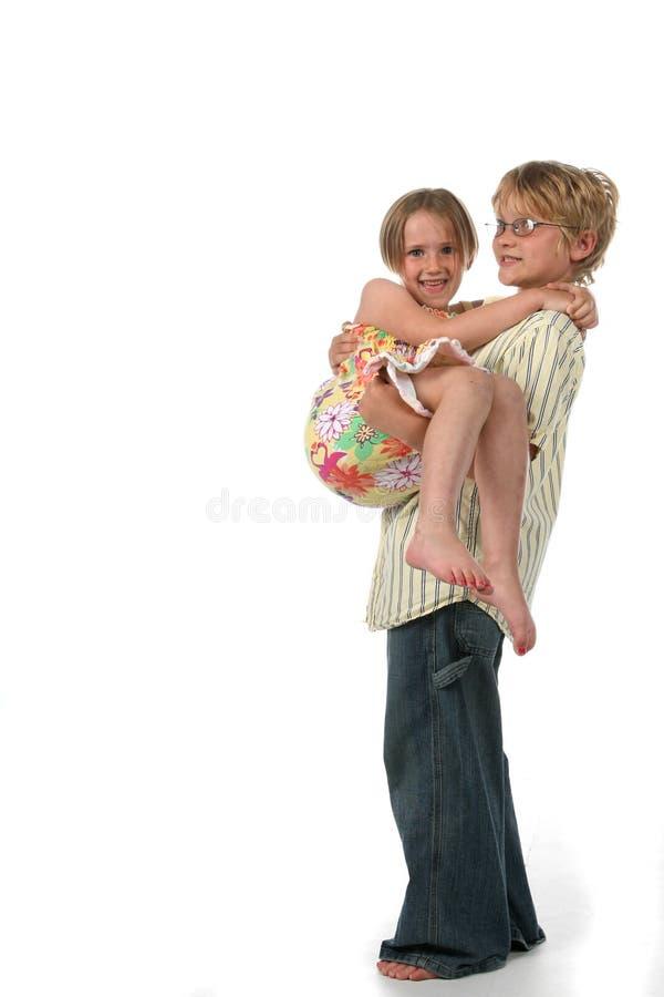 Grote broer die zijn kleine zuster houdt stock afbeelding