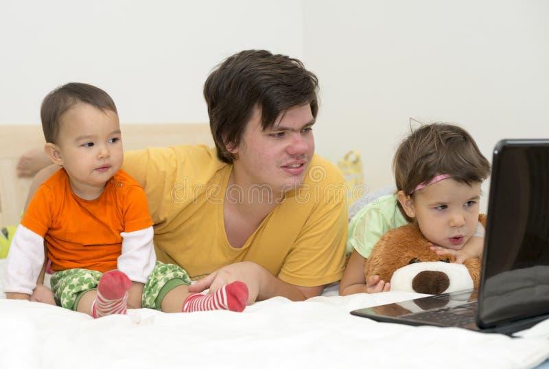 Grote broer het letten op beeldverhalen met zijn jongere zusters bij laptop stock foto