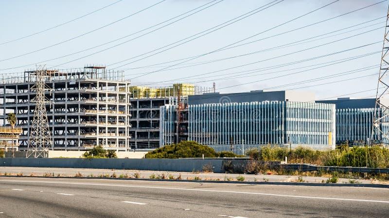 Grote bureaugebouwen in aanbouw naast elektriciteitstorens; snelweg zichtbaar in de voorgrond; Silicon Valley, San stock foto's