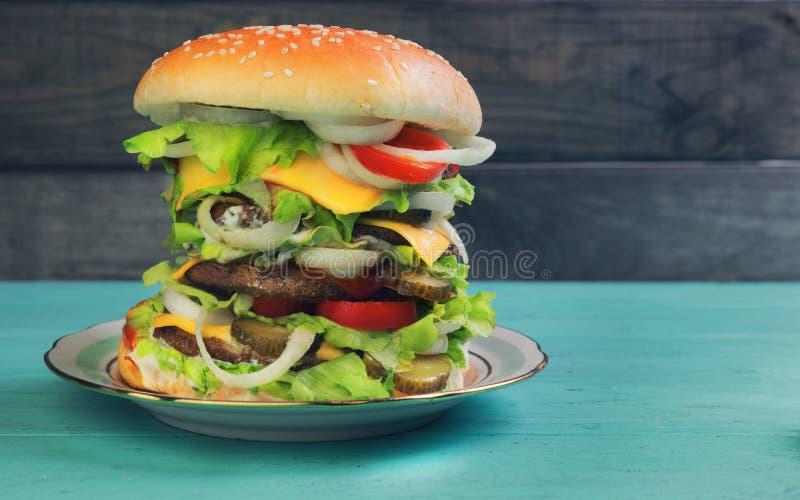 Grote cheeseburger luxehoogte op groene houten achtergrond stock afbeelding