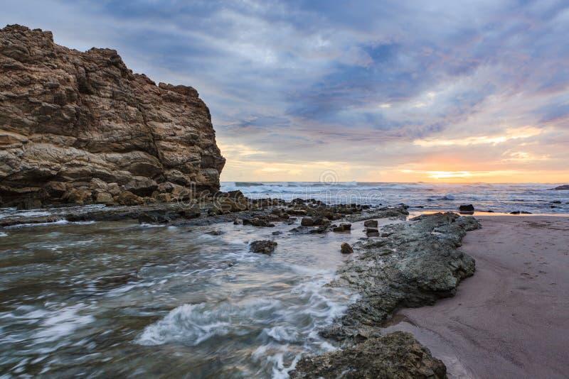 Grote de zonsondergang lange blootstelling van het rotsstrand royalty-vrije stock foto's