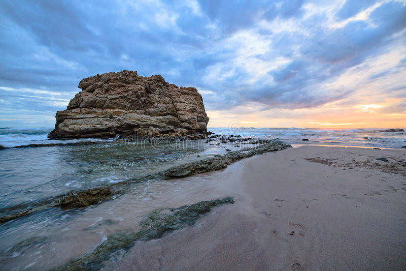 Grote de zonsondergang lange blootstelling van het rotsstrand stock foto