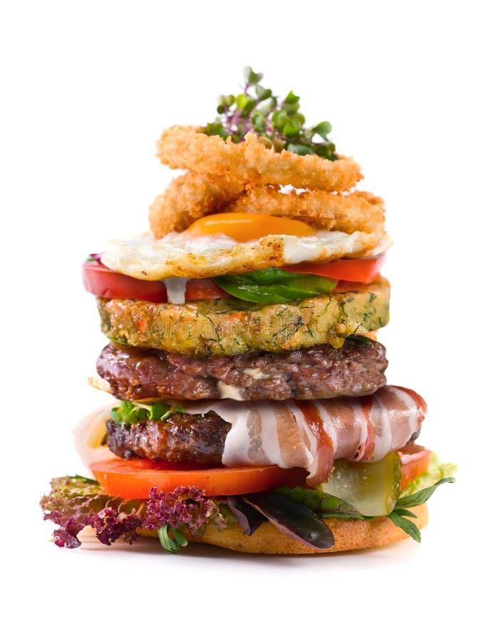 Grote die hamburger op witte achtergrond wordt geïsoleerd stock afbeelding