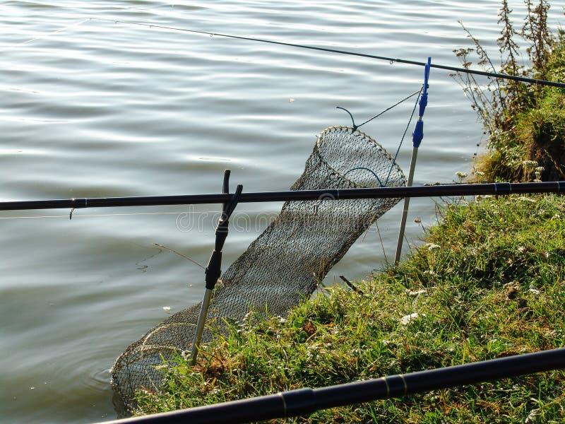 Grote die visserijkooi in het water en de hengels op de waterkant wordt verminderd royalty-vrije stock foto's