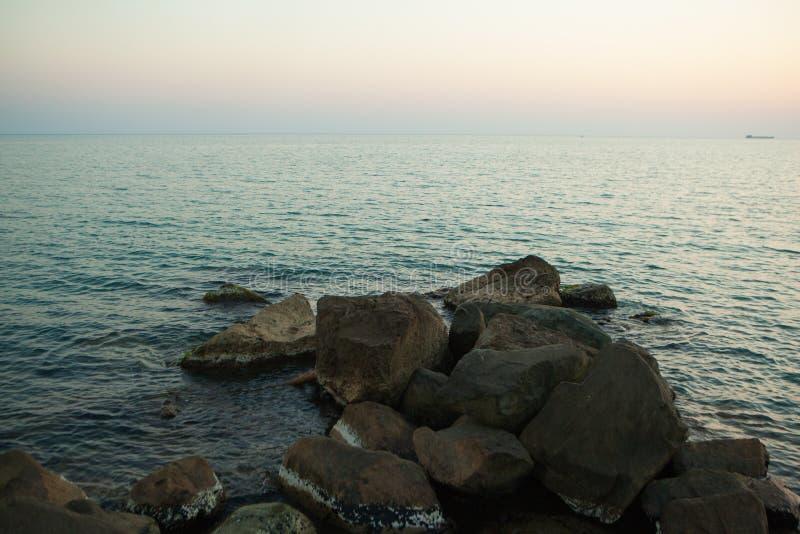Grote donkere stenen die in het overzees liggen stock foto's
