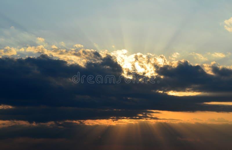 Grote donkere wolk met zonnestralen op hemel bij avond stock fotografie