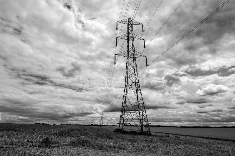 Grote elektriciteitspyloon met pylonen in de afstand op een gebied van graanstoppelveld - zwarte & wit stock afbeelding