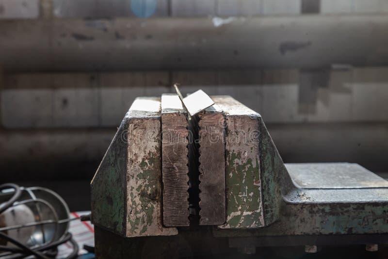 Grote en krachtige groene bankschroef met overweldigde verf op een blauwe werkbank voor metaal en het houten werk in de workshop  stock foto