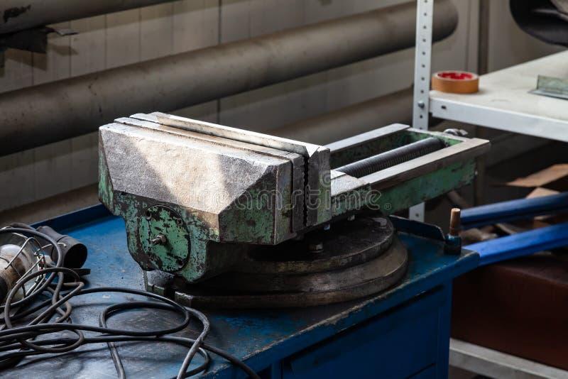 Grote en krachtige groene bankschroef met overweldigde verf op een blauwe werkbank voor metaal en het houten werk in de workshop  royalty-vrije stock foto's