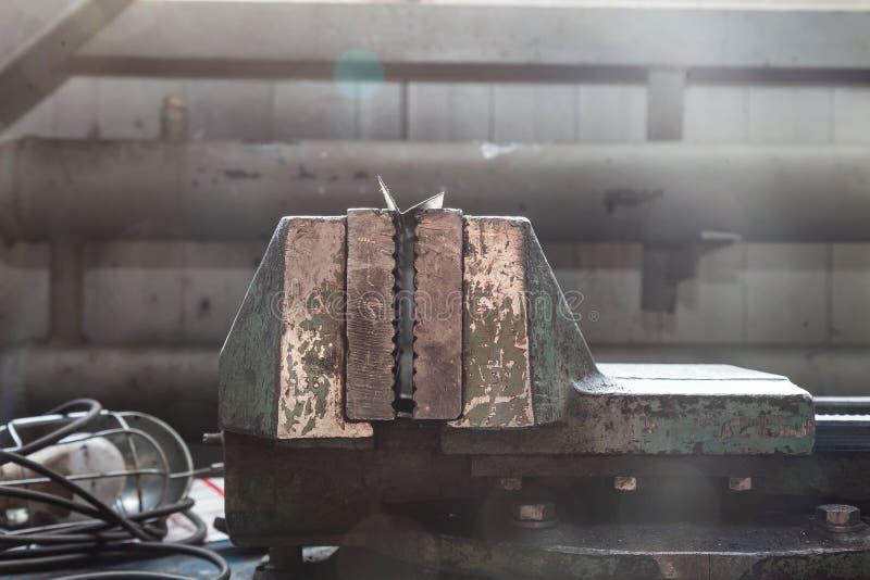 Grote en krachtige groene bankschroef met overweldigde verf op een blauwe werkbank voor metaal en het houten werk in de workshop  stock foto's
