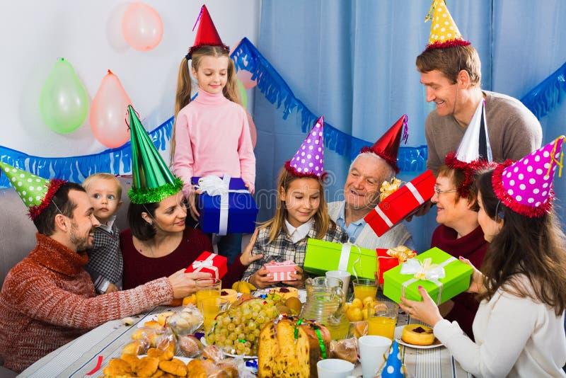 Grote familie die giften voorstellen aan meisje tijdens verjaardagspartij royalty-vrije stock fotografie