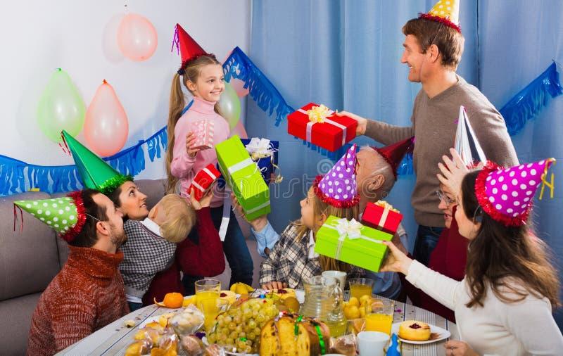 Grote familie die giften voorstellen aan meisje tijdens verjaardagspartij stock afbeeldingen