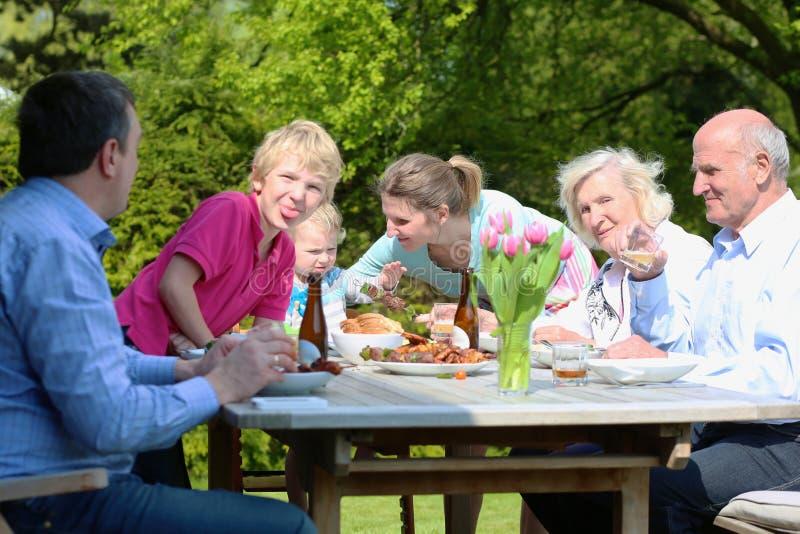 Grote familie die lunch in de tuin hebben stock afbeeldingen
