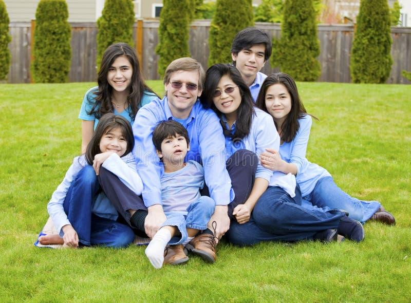 Grote familie van zeven die samen op gazon zitten stock foto
