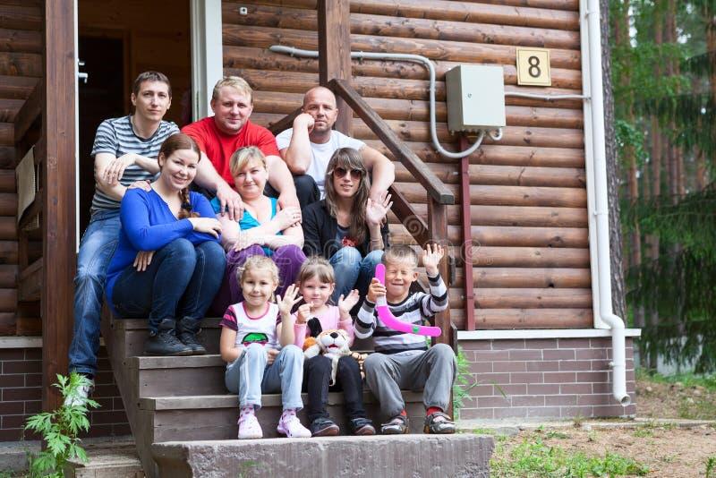 Grote familiezitting op de huisportiek royalty-vrije stock foto