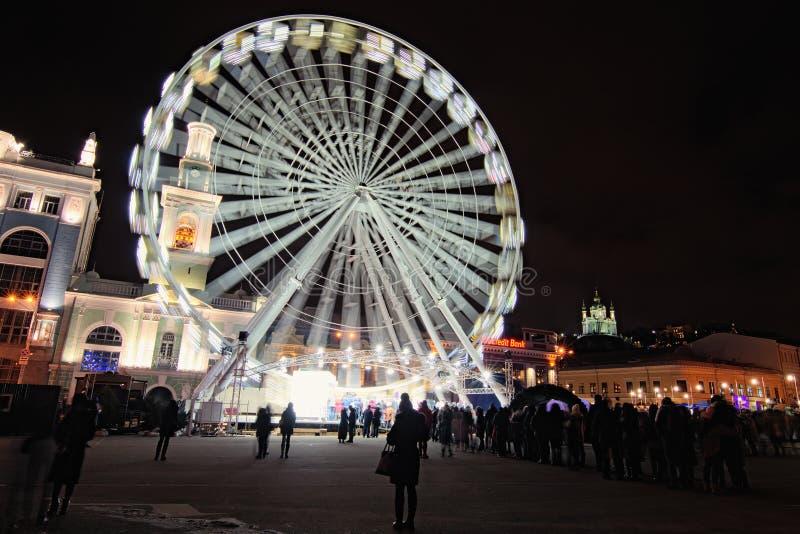 Grote ferris rijden bij Kerstmismarkt ` s bij het Kontraktova-Vierkant in Kyiv, de Oekraïne De mening van de de winteravond royalty-vrije stock foto