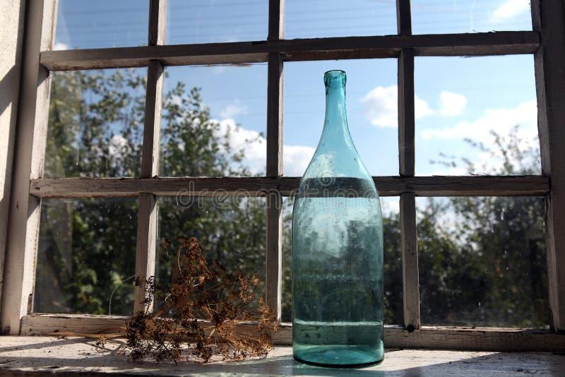 Grote fles bij het venster stock afbeelding