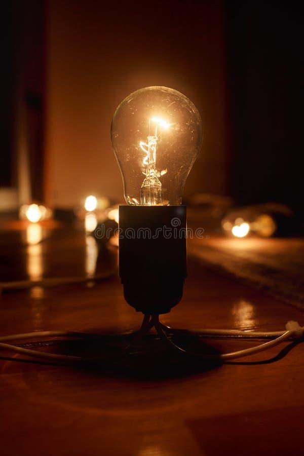 Grote geborstelde elektrische gloeilamp op de vloer, tegen een donkere achtergrond Licht in Duisternis royalty-vrije stock afbeelding