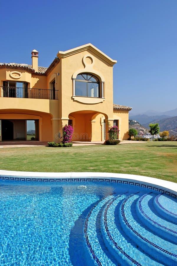 Grote gele zonnige Spaanse villa met pool en blauwe hemel stock fotografie