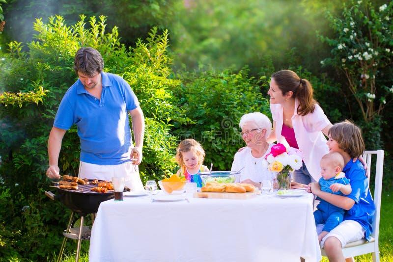 Grote gelukkige familie die bbq van grill in de tuin genieten stock fotografie