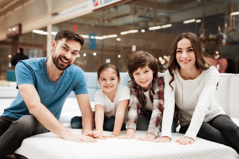 Grote gelukkige familie die orthopedische matras in winkel van meubilair testen Controlezachtheid van matras stock afbeeldingen