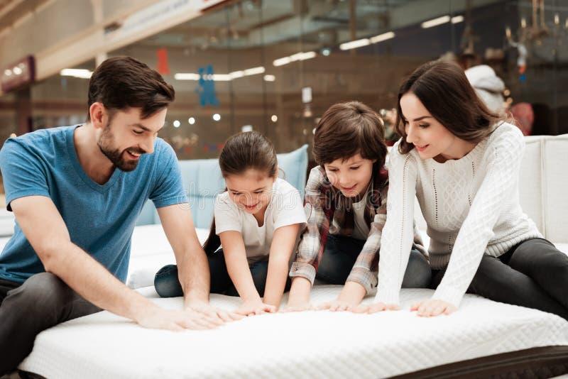 Grote gelukkige familie die orthopedische matras in winkel van meubilair testen Controlezachtheid van matras royalty-vrije stock afbeelding