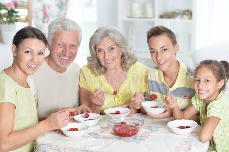 Grote gelukkige familie die verse aardbeien eten bij keuken stock afbeelding