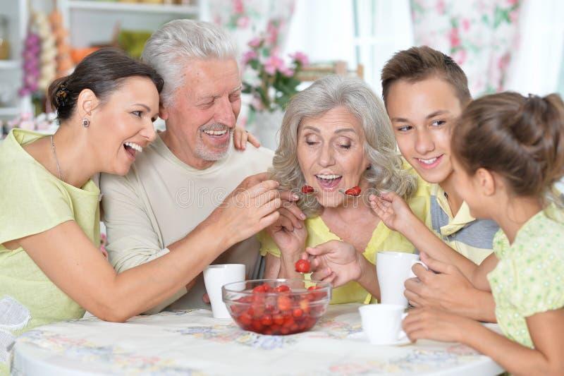 Grote gelukkige familie die verse aardbeien eten bij keuken stock foto's