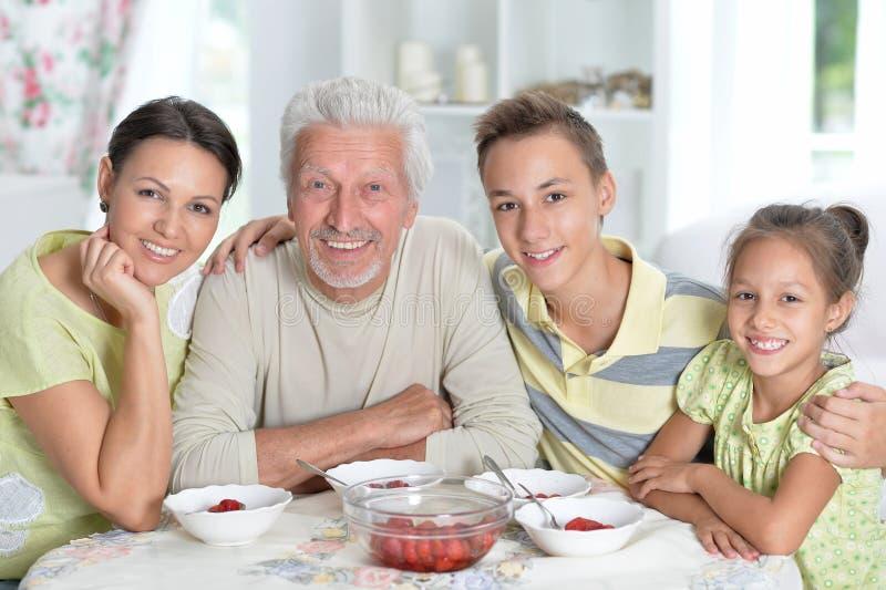 Grote gelukkige familie die verse aardbeien eten bij keuken royalty-vrije stock afbeeldingen