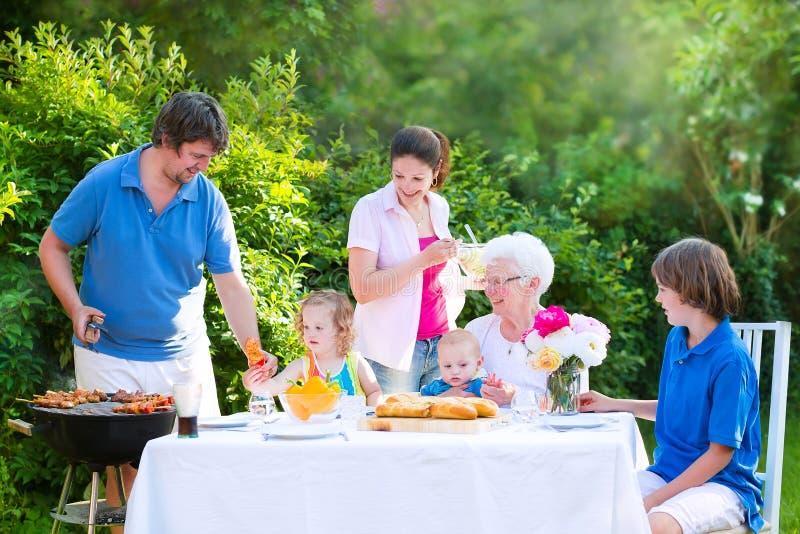 Grote gelukkige familie die vlees met grootmoeder roosteren royalty-vrije stock foto