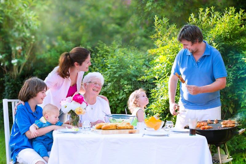 Grote gelukkige familie die vlees voor lunch roosteren stock fotografie