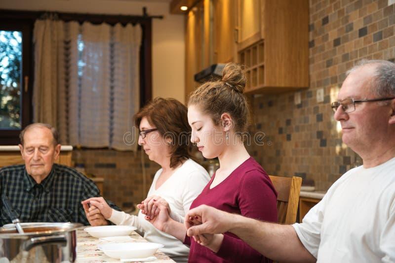 Grote generatiefamilie die bij diner bidden stock foto's