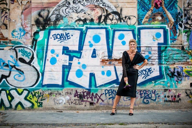 Grote glimlach van een elegante dame voor een muur met graffiti Een muur vernielde met het art. van de straatgraffiti stock afbeelding