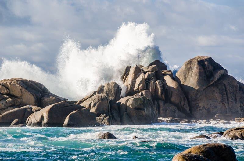 Grote golven die op rotsenkustlijn verpletteren stock afbeelding