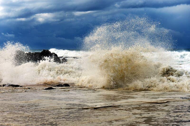 Grote golven die over rotsen dichtbij kust verpletteren royalty-vrije stock afbeeldingen