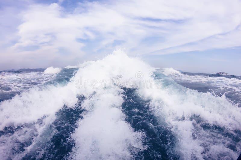 Grote golven van de motor achter de motorboot op volle zee Blauwe hemel met witte wolken royalty-vrije stock afbeeldingen