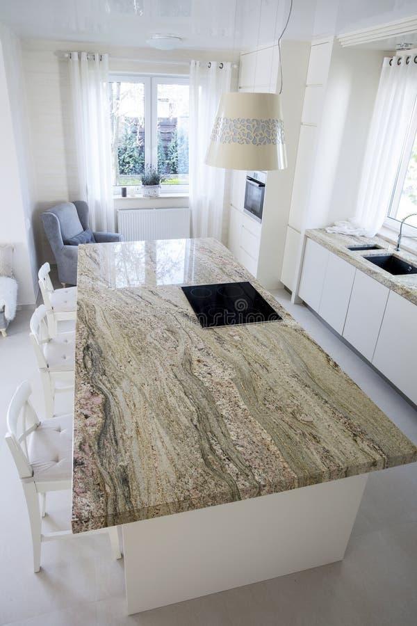 Grote granietachtige worktop in heldere keuken royalty-vrije stock afbeelding