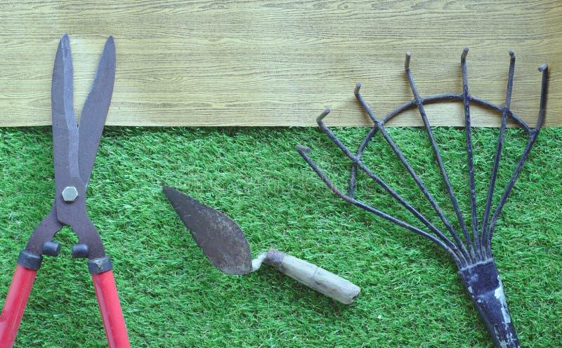 Grote gras scherpe schaar, rood handvat, staalhark, staaltroffel, gravend Gazon Bruin houten teken als achtergrond stock afbeeldingen