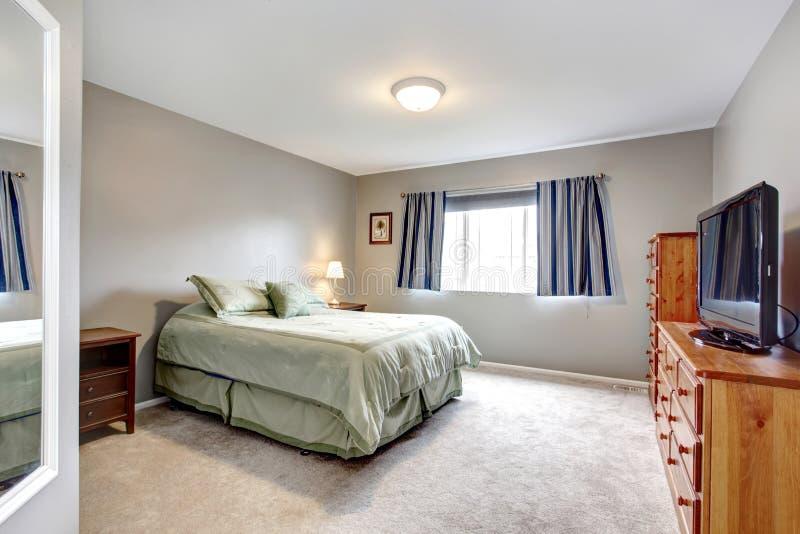 https://thumbs.dreamstime.com/b/grote-grijze-slaapkamer-met-opmaker-tv-en-blauw-gordijnen-en-groene-beddegoed-29838524.jpg