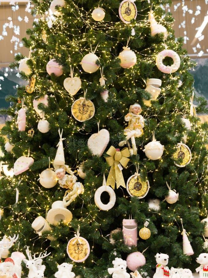 Grote groene Kerstboom met witte en gele decoratie Gouden speelgoed op feestelijke pijnboomboom Giftenconcept De lichten van de k royalty-vrije stock fotografie