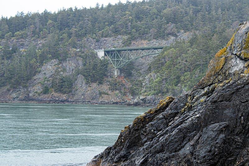 Grote groene overspannen brug over kustklippen stock fotografie