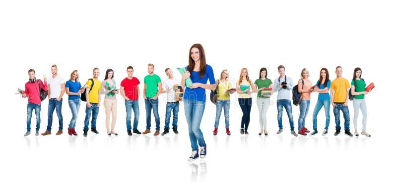 Grote groep glimlachende vrienden die samen en camera bekijken blijven die op witte achtergrond wordt geïsoleerd royalty-vrije stock afbeelding