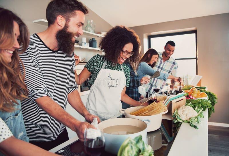 Grote groep van zes vrienden die deegwaren koken bij lijst royalty-vrije stock afbeeldingen