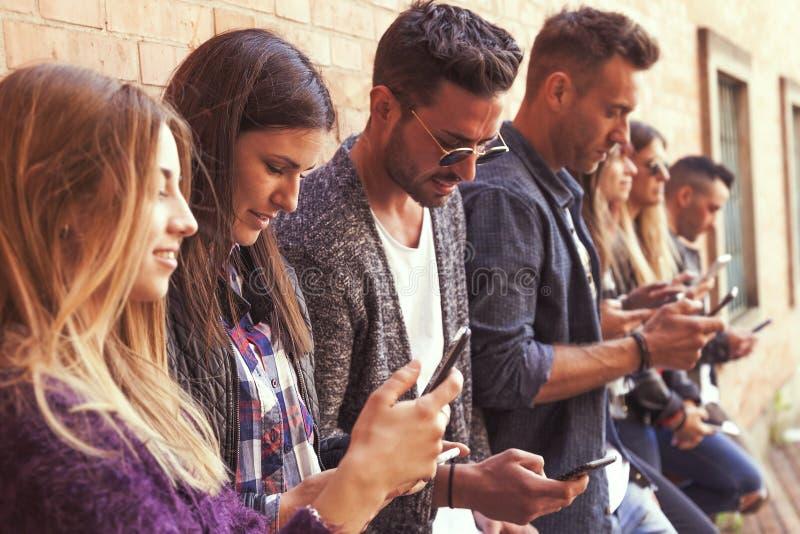 Grote groep vrienden die slimme telefoon met behulp van tegen een rode muur royalty-vrije stock afbeeldingen