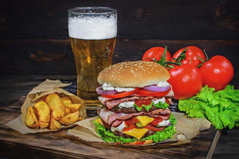 Grote Hamburger en licht bier op een houten lijst royalty-vrije stock foto