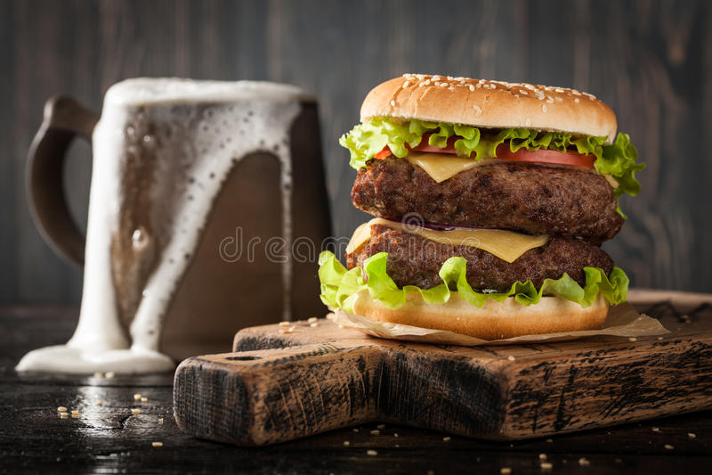 Grote hamburger en mok bier stock afbeelding