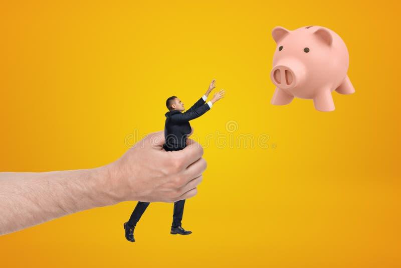 Grote hand kleine zakenman houden die uit bereikend met zijn beide handen voor leuk roze spaarvarken die in lucht drijven op ambe royalty-vrije stock afbeeldingen